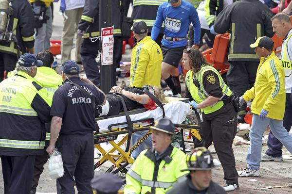 Rescue workers tend to the injured after two bombs went off near the Boston Marathon finish line on Boylston Street.