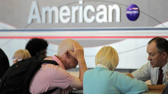 Travelers talk to an American Airlines ticket agent at O'Hare International Airport in an October 2012 file photo.