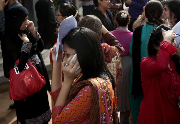 People evacuate buildings and call their relatives after an earthquake was felt in Karachi, Pakistan.