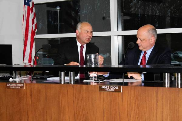 Orland Park Trustee Ed Schussler discusses the tentative refuse contract with Trustee Jim Dodge prior to Monday's Village Board meeting. Schussler, who chairs the board's Public Works Committee, recommended authorizing staff to negotiate a 10-year contract with Alsip-based Waste Management Illinois.