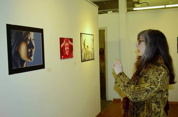 Artist Laura Young of West Chicago admires Nicole Clark's - Vanitas Self Portrait at an art show for high school students.