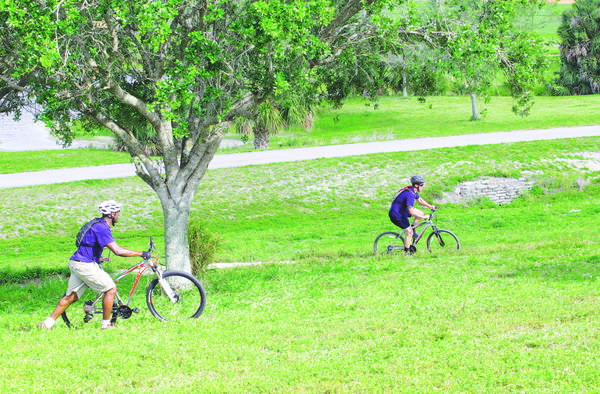 Daminan Reynolds, left, gives pointers to Robert Hack at Dyer Park. The park, built atop an old landfill in West Palm Beach, has paved paths and unpaved trails. Photo by Kara Starzyk.