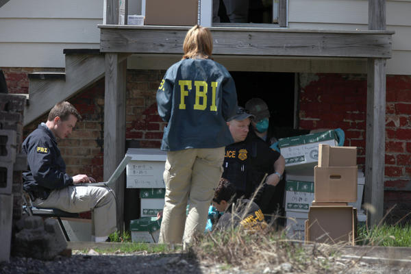 FBI agents and law enforcement officials remove documents from a building adjacent to Sacred Heart Hospital.