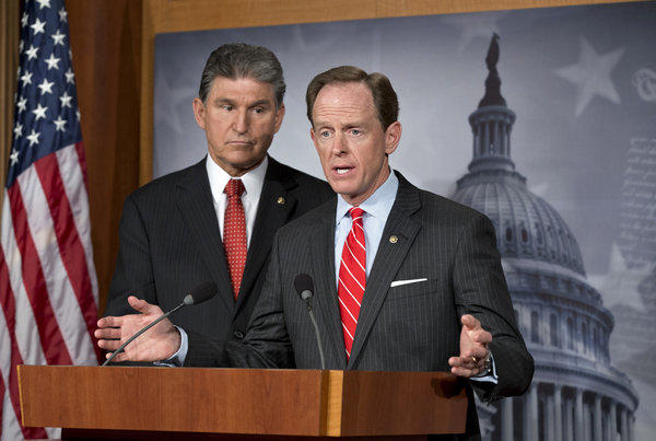Democratic Sen. Joe Manchin III of West Virginia, left, and Republican Sen. Patrick J. Toomey of Pennsylvania talk about their proposal on expanding background checks to more gun buyers at the Capitol in Washington.