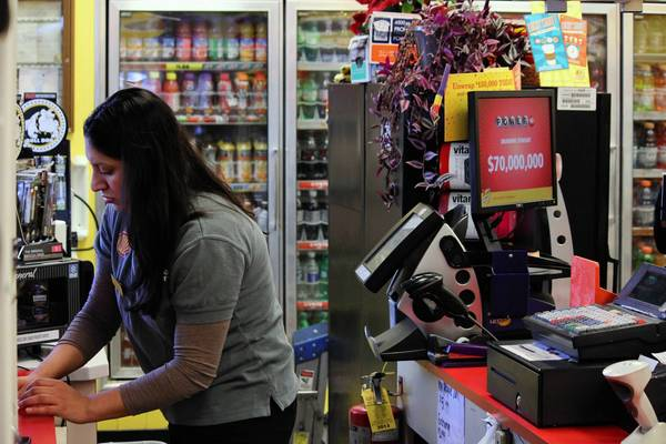 Evelyn Solano works the cashier at the Shell gas station in downtown Lake Forest in February. The owner of the station is pushing the city to lift its ban on alcohol sales at gas stations.