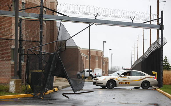 South Bend Tribune/SANTIAGO FLORES St. Joseph County police guard the gate at the county jail where an inmate used a bread truck to break through and escape early this morning.