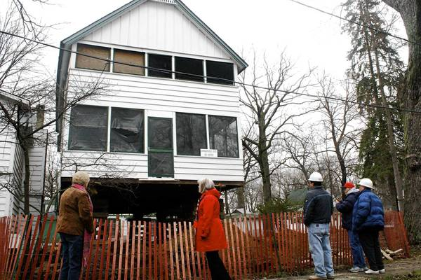 Contractors and representatives from the Methodist Church and Methodist CampGround in Des Plaines survey one of six historic cottages being raised to avoid flooding from the nearby Des Plaines River.