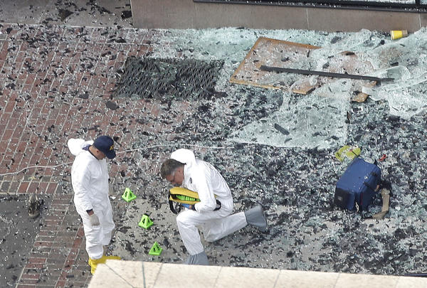 Two men in hazardous materials suits put numbers on the shattered glass and debris as they investigate the scene at the first bombing on Boylston Street in Boston.