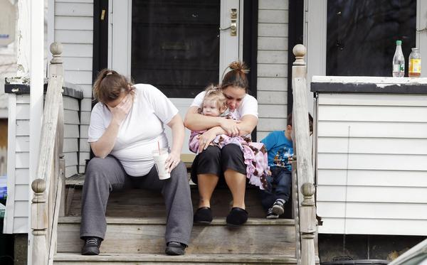 Grieving neighbors sit outside the house of Krystle Campbell's parents in Medford, Mass., on Tuesday. Campbell was killed in Monday's explosions at the finish line of the Boston Marathon.