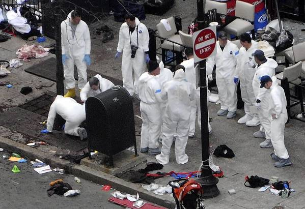 Investigators in white jumpsuits Tuesday work the crime scene on Boylston Street following Monday's bomb attack at the Boston Marathon.