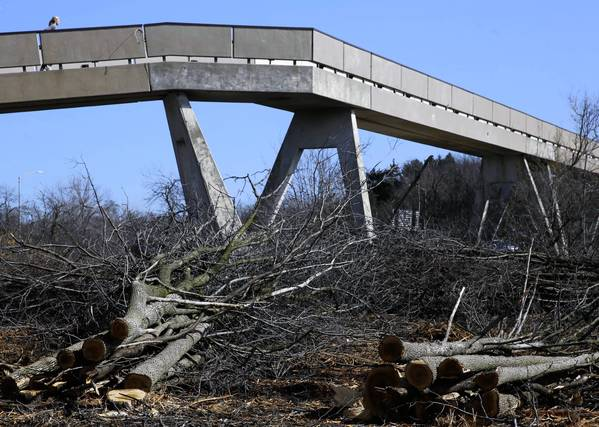 A woman runs across a pedestrian bridge near Old Skokie Road and Old Deerfield Road in Highland Park, IL on Tuesday, April 16, 2013. Near this bridge and along parts of Route 41, hundreds of trees have been cut down concerning residents in the area.
