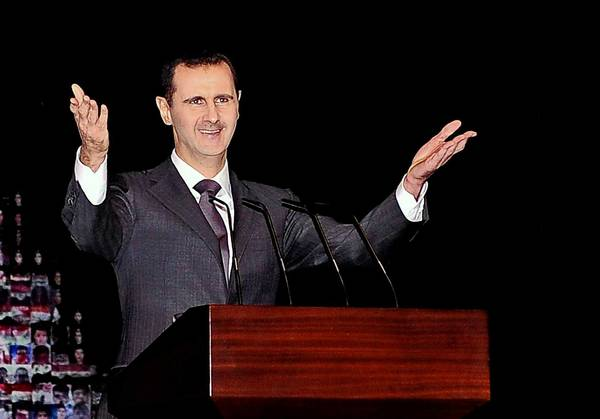 Syrian President Bashar Assad, shown in January, has reduced prison terms for thousands of inmates.