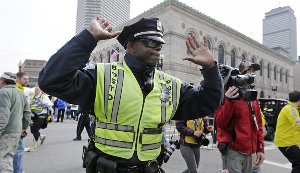 A Boston police officer clears Boylston Street following an explosion at the finish line of the 2013 Boston Marathon.