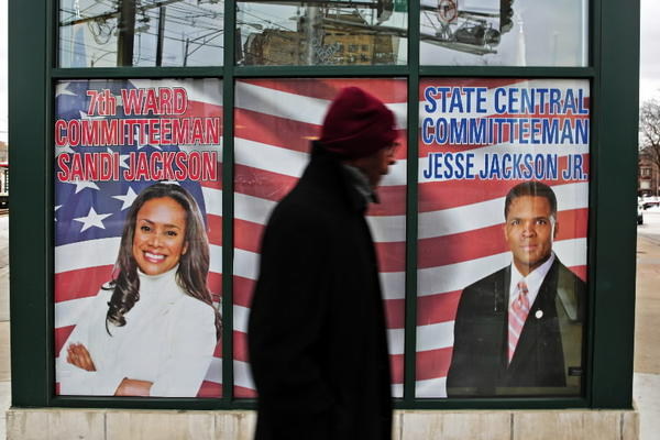 A man walks past window decal of former Rep. Jesse Jackson Jr. and his wife Sandi at the former politicians' headquarters Saturday, Feb. 16, 2013 at the intersection of Yates Boulevard and Exchange Avenue in Chicago.