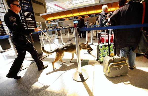 Los Angeles Airport Police Officer Daniel Keehne and an explosives detection dog monitor baggage and passengers at the Tom Bradley International Terminal at LAX on Tuesday, the day after the bombing at the Boston marathon.