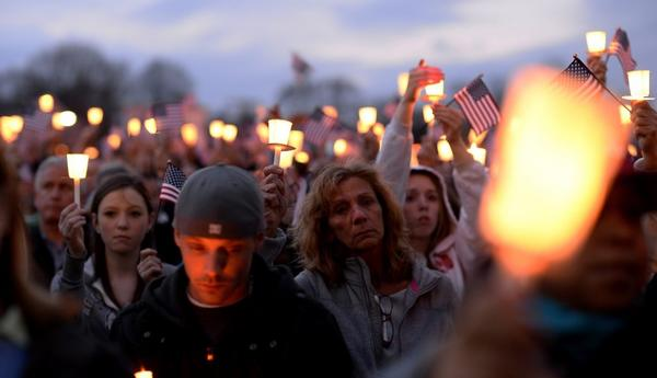Residents hold aloft American flags and candles during an outdoor candlelight service for 8-year-old Martin Richards in Boston.