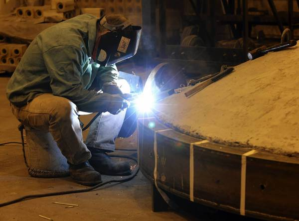 A worker welds machinery at the new steel plant on East 93rd Street in Chicago's Burnside neighborhood. The company says it has moved 60 percent of its operation from its North Side facility near Southport Avenue and Kingsbury Street. The move is expected to be complete by year's end.