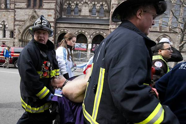 Firemen carry an injured person where two explosions occurred along the final stretch of the Boston Marathon on Boylston Street in Boston on Monday.