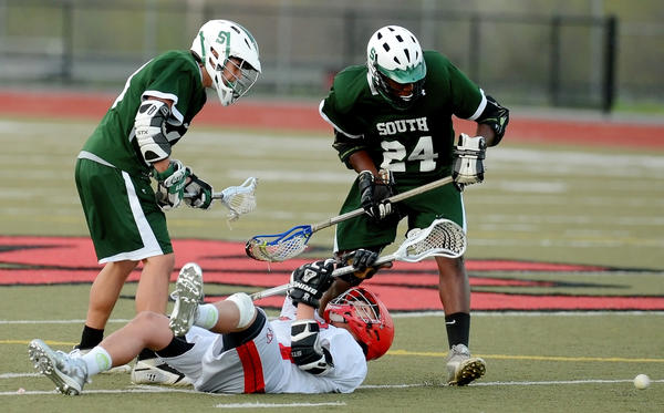 North High's Reggie Daniel, bottom, loses the ball after being hit by South High's Noah Wright, left, and Josiah Johnson in the first period.