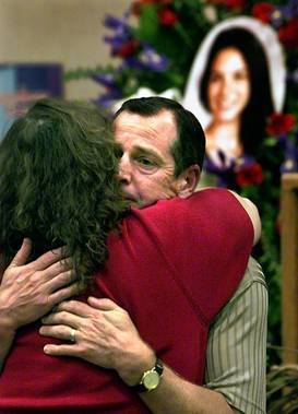 Tom Frost gets a hug from a friend during a ceremony in 2001 honoring his daughter Lisa, rear right, who died in the 9/11 attacks.