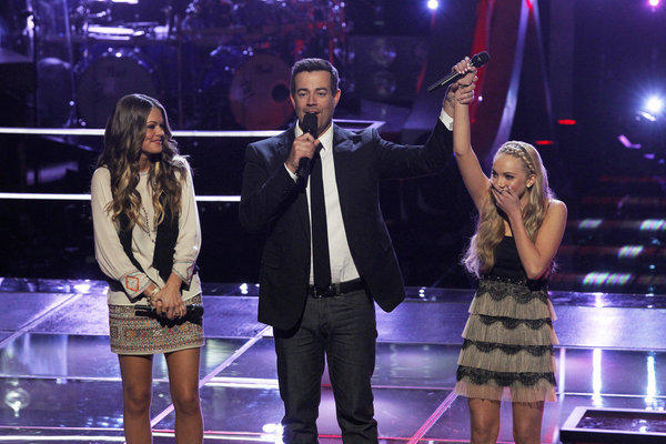 "Caroline Glaser, left, Carson Daly and Danielle Bradbery take the stage in ""The Voice"" battle rounds."