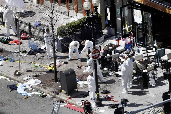 Investigators in protective suits examine the scene of one of the bomb blasts near the finish line of the Boston Marathon.