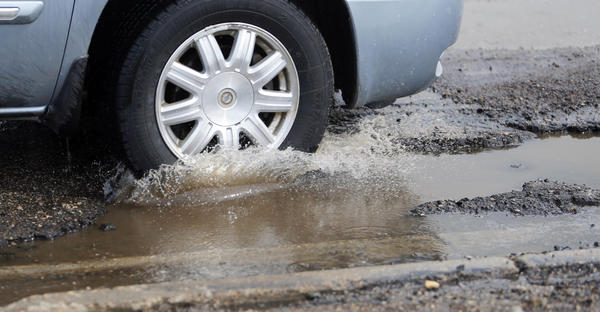 A tire splashes into a water filled pot hole on South Wilson Street just south of Third Avenue Southeast Tuesday. photo by john davis taken 4/16/2013