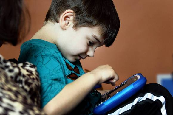 Cristian Reilly plays with a digital tablet on his mother's lap in Milwaukee.
