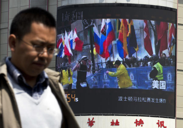 A Chinese man in Beijing walks past a huge screen reporting on the Boston Marathon bombings. One of the three people killed has been identified as a Chinese national studying in the U.S.
