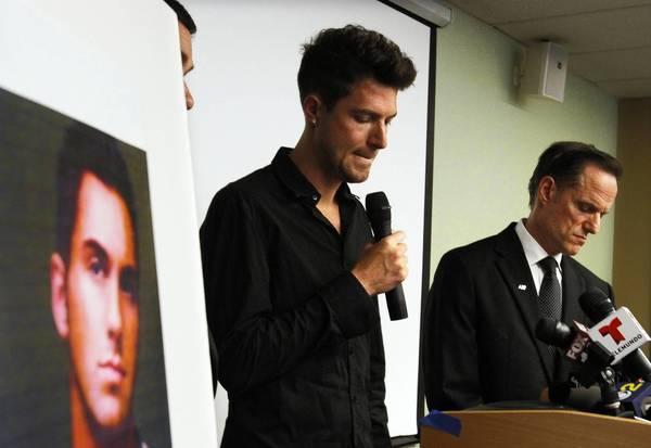 Casey Hayden speaks about his partner Rjay Spoon, in photo at left, who died of bacterial meningitis, as Michael Weinstein, right, president of the AIDS Healthcare Foundation listens during a news conference in West Hollywood.