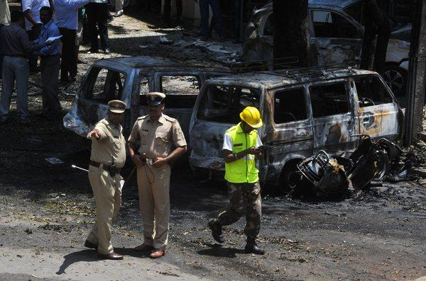 Police and forensic experts inspect the site of a bomb blast near a Bharatiya Janata Party office in Bangalore, India.