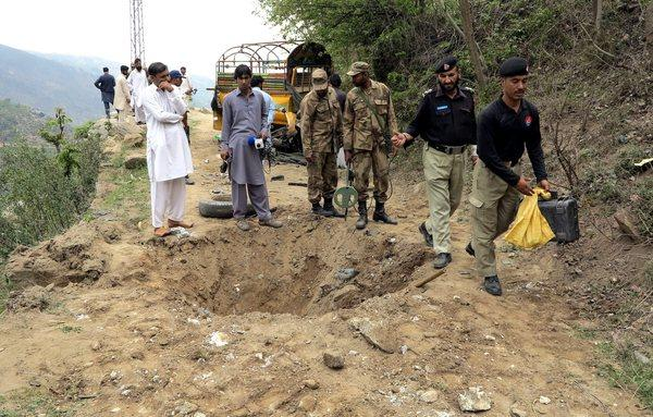 Pakistani security officials inspect the site of a bomb blast Sunday that targeted the vehicle of Mukarram Shah, a local leader of Awami National Party, in Pakistan's Swat Valley.