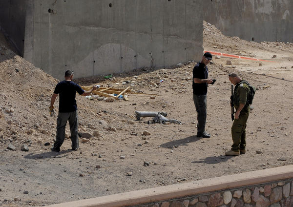 Israeli security officers investigate the scene of a rocket attack in Eilat.