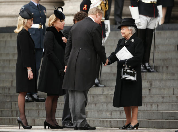 Queen Elizabeth II shakes hands with Mark Thatcher as they leave the funeral of former British Prime Minister Margaret Thatcher at St. Paul's Cathedral in London.