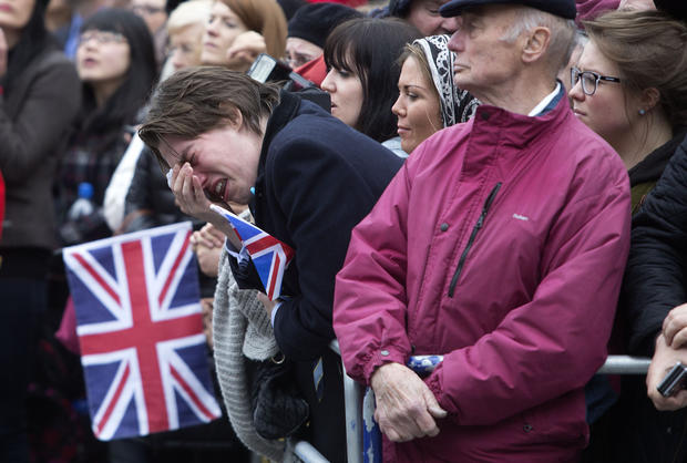 A member of the public weeps as the coffin of Baroness Thatcher is carried out of St. Clement Danes church.