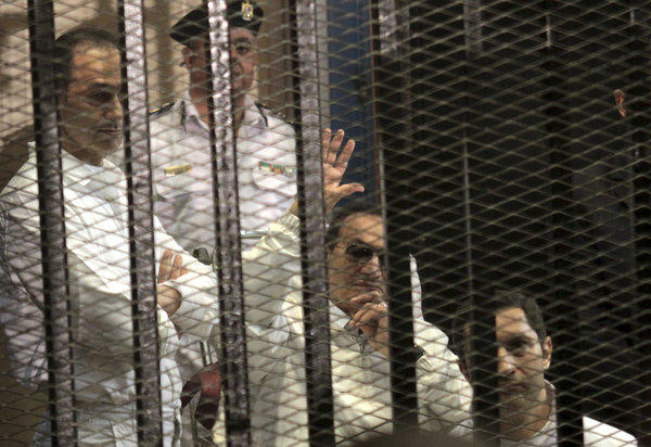 Former Egyptian President Hosni Mubarak waves at his supporters during a court appearance Saturday. Also in attendance were his sons: Alaa, right, and Gamal, left.