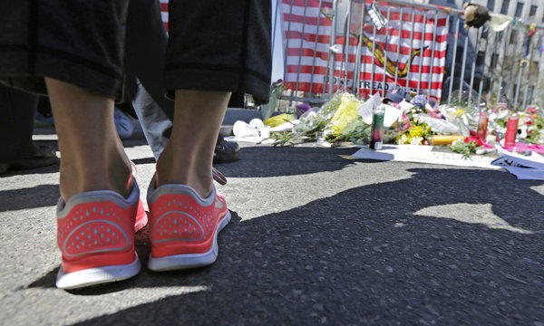 A woman in running shoes pauses at a makeshift memorial on Boylston Street near the finish line of Monday's Boston Marathon explosions.