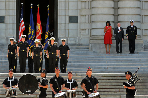 On the steps of Bancroft Hall, First Lady Michelle Obama, left, with U.S. Secretary of the Navy Ray Mabus, center, and Commandant of Midshipmen, Capt. Bob Clark, right, review midshipmen at the United States Naval Academy.