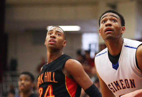 Simeon's Jabari Parker stands between Oak Hill Academy's R.J. Curington (24) and Rokas Gustys (33) during the second half of their team's game in the Hoop Classic tournament in Springfield, Mass., in January.