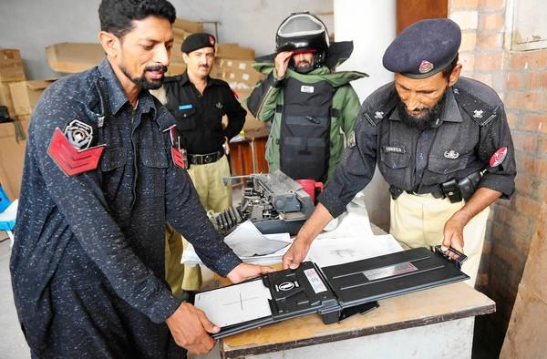 Officers at the headquarters of the bomb squad in Peshawar, Pakistan, develop an X–ray of an explosive device in 2011.