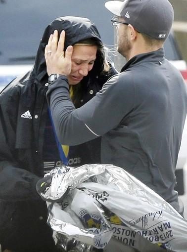 An unidentified Boston Marathon runner is comforted as she cries in the aftermath of two blasts that exploded near the finish line of the Boston Marathon. Hundreds of heroes emerged in the chaos caused by the explosions.