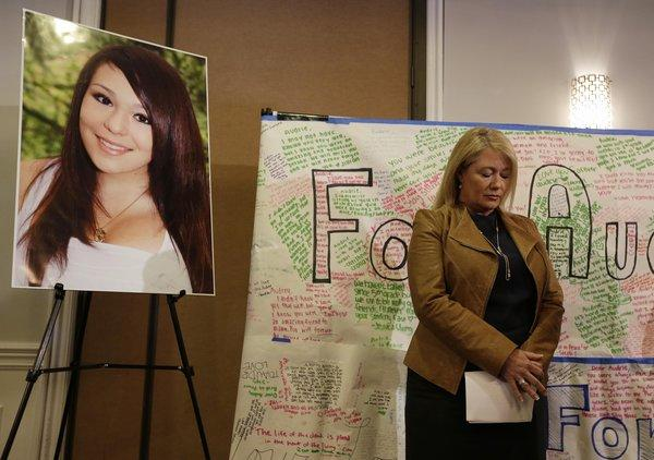Sheila Pott, mother of Audrie Pott, who committed suicide after a sexual assault, stands by a photograph of her daughter and a message board during a news conference on Monday in San Jose.