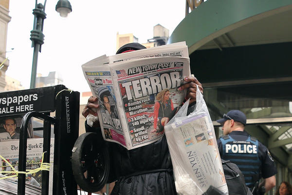 A woman reads the New York Post as police stand guard outside Penn Station in New York City.