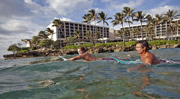 Boarders paddle the surf near the Turtle Bay Resort on Oahu's North Shore. Turtle Bay, the North Shore's only large hotel, is renovating its 397 guest rooms and suites, two restaurants and spa. The overhaul began in January and should be completed in mid-October.