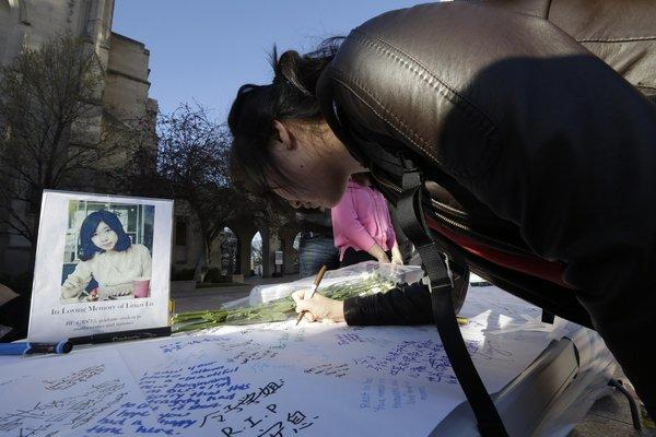 A photograph of Boston University student Lu Lingzi, who was killed in the Boston Marathon explosions, is on a table as a student writes a message on a board outside the school's Marsh Chapel before a vigil Wednesday.