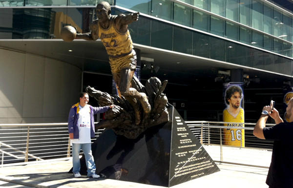 Lakers fan Luis Ramirez gets his photo taken at the Magic Johnson statue outside Staples Center on Wednesday evening.