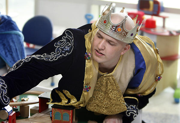 """Peninsula Catholic senior Darrell Wood is finishing up his chemo treatment at Children's Hospital of the King's Daughters in Norfolk. He is a cast member in Peninsula Catholic's production of """"Beauty and the Beast"""". His fellow cast members are joining him in costume to visit patients. Here he is playing with a young patient."""