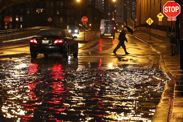 A pedestrian crosses West Grand Avenue as cars navigate a flooded portion of the roadway caused by persistent rains in the Chicago area.
