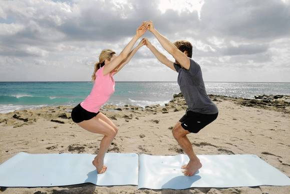 Face each other with your arms fully extended in front of you, holding hands with your partner. Both should be standing on tiptoes and holding that position for 3 seconds. Next, both should drop into a chair position by bending your knees, squatting down and pushing your behind backward until your thighs are parallel to the floor. While doing this, you should still be on your tiptoes holding hands. Hold the chair position for 3 seconds before lifting back up to the starting position on your toes. Repeat 10 times.