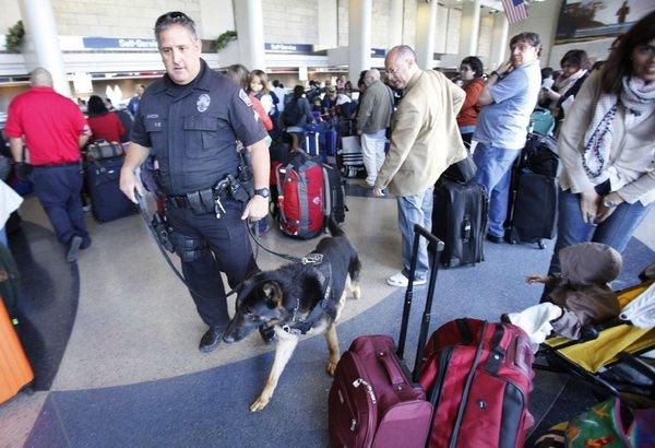 Los Angeles Airport Police officer Mike Garzon with explosives detection dog Erik monitor baggage and passengers at American Airlines Terminal 4 at LAX on Tuesday, a day after the bombing in Boston. The Transportation Security Administration says that, despite the attacks this week, it will loosen regulations on some objects that can be carried on planes, including small knives.